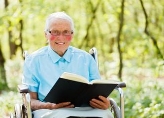 Bible Read by Elderly in Wheechair