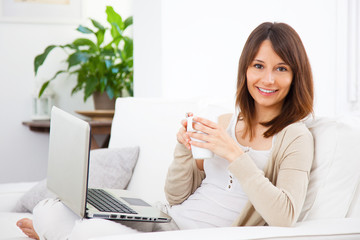 Young woman take a coffee and working at home