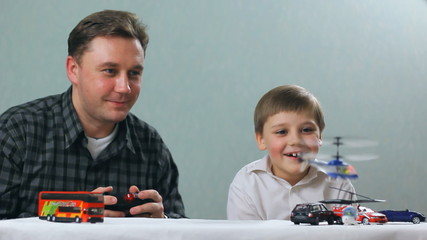 father and son playing a toy helicopter. Home family vacaton