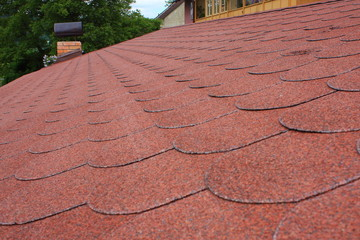 Red asphalt shingle roofing on a roof and chimney