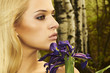 Beautiful blond woman with blue flowers in a forest