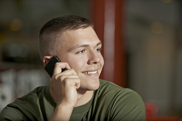 Young man talking on smartphone and smiles