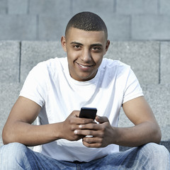 Young holding a smartphone and smiles
