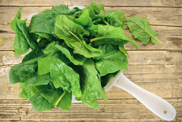 Spinach leaves in the strainer on wood background.