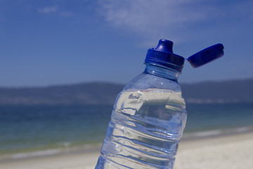 Open water bottle on the beach