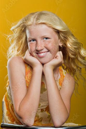 Beautiful blond girl with freckles sitting on a chair and smilin