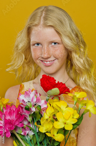 Beautiful blond girl with freckles holding a bouquet of flowers