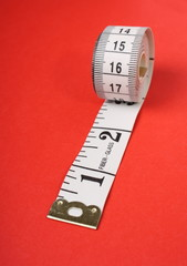 Rolled up Tape Measure on Red Background
