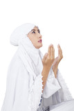 Beautiful muslim woman praying on white