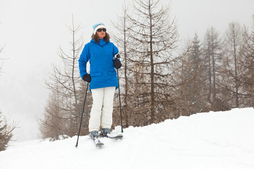 Happy ski woman standing in snow with pine trees.