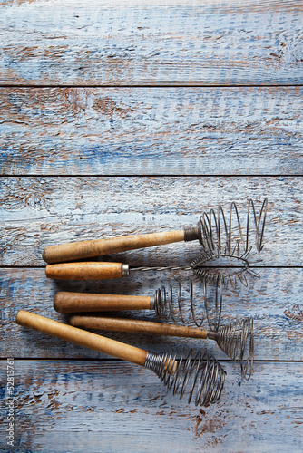 retro kitchen utensils whisks  on old wooden table