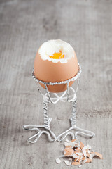 Boiled egg in an eggcup on wooden background.