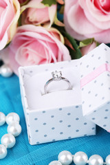 Rose and engagement ring on blue cloth