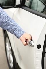 Man hand opening car door, close up