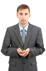 Young businessman with coins and plant isolated on white.