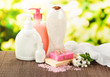Cosmetics bottles and natural handmade soap on green background
