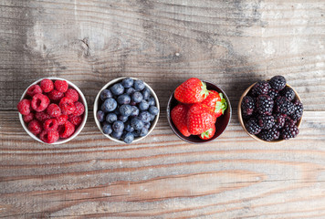 A four bowls overflowing with summer berries