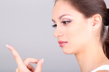 Young woman putting contact lens in her eye on grey background