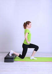 Beautiful young woman exercises on stepper