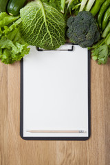 Low angle view of a notebook on wooden table with vegetables.