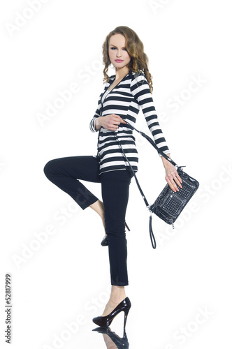 Pretty young woman in stripy shirt with bag posing