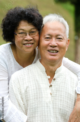 happy asian senior couple embracing each other