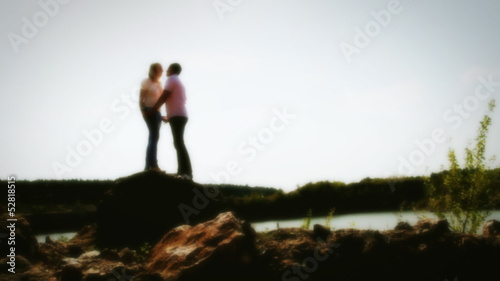 romantic couple of lovers on the rocks, defocused