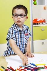 Little boy wearing glasses and draw with crayons