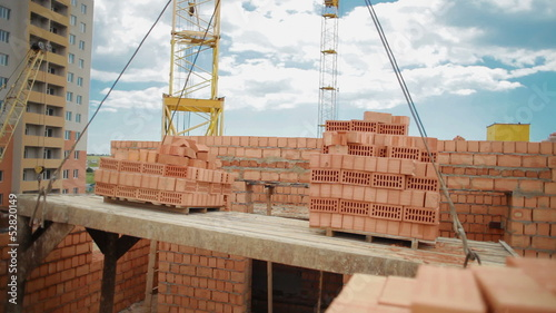 Crane carries bricks at a construction site