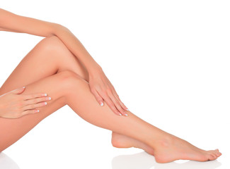 Smooth skin on female legs. White background, copyspace.