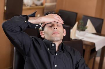 Mann im Restaurant fasst sich an Stirn
