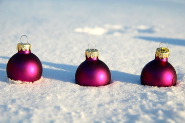 drei Weihnachtskugeln im Schnee