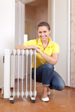 Happy woman near oil heater