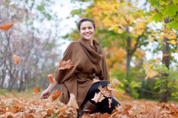 Girl throws maple leaves