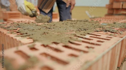 builder lays bricks on a construction site