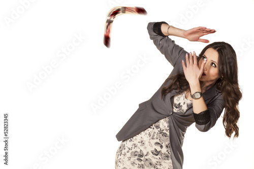 Poster woman defending herself with her hands from the boomerang