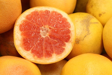 Whole grapefruits with one cut open and displayed on top