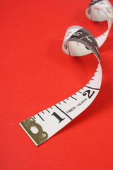 Curled White Tape Measure on Red