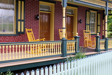 Colorful brick faced front porch and rocking chairs