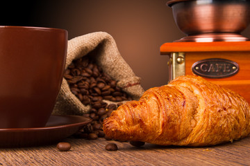 Coffee cup with a croissant and fresh coffee beans