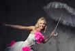 Beautiful bride with lace umbrella posing indoors