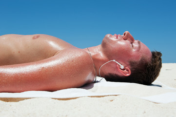 Man sunbathes and listens to music on the beautiful beach