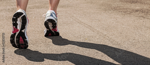 Woman legs in sneakers on asphalt