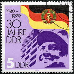 stamp printed by Germany, shows DDR Arms and Flag Worker