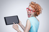 Emotional red-haired girl holding  tablet computer.