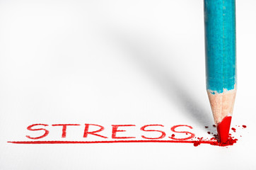 Red pastel pencil writing the word Stressed out