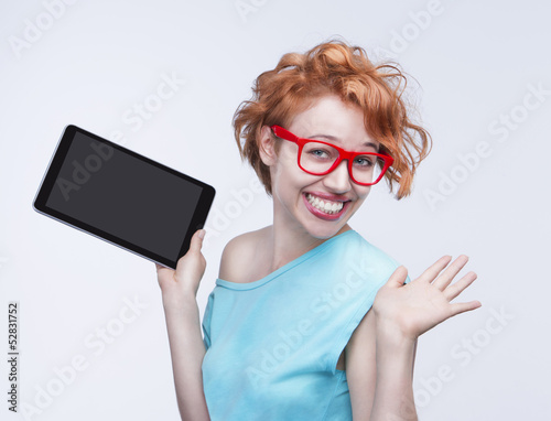 Emotional red-haired girl holding tablet computer