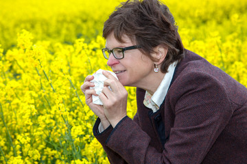 Woman with hay fever on blooming rapeseed field