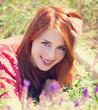 Redhead girl at green grass at village outdoor