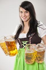junge freundliche Kellnerin im Dirndl mit Maß Bier
